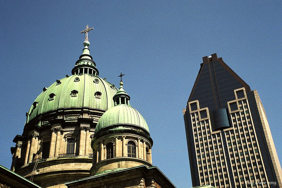 We can see on the left the basilique Marie Reine du Monde and on the right the building &quot...