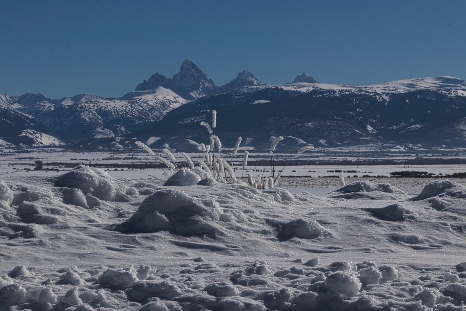 A shot of Le Trois Tetons in the background, the snow covered Snake River Valley near Tetona, Ida...