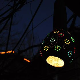 The sun was down and it was getting dark. The gourd lamp was spreading light out of colorful holes. It was nice scene at dark.