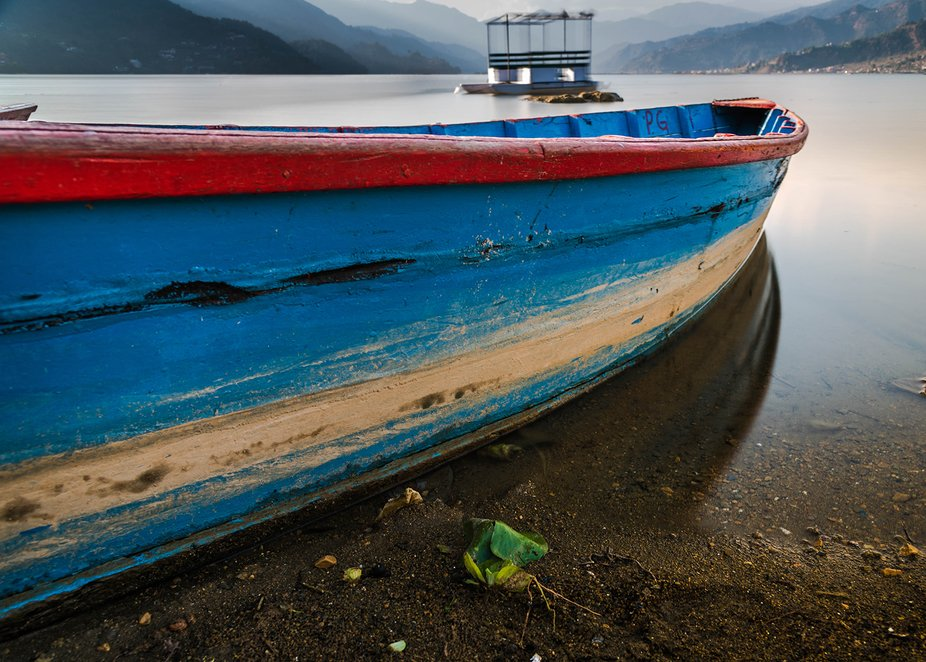 A boat was resting on Phewa Lake, Pokhara Nepal.