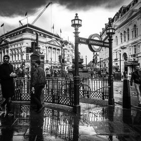 After a long day of photojournaling in the rain in London, I came across reflections of people and tube station gates in Piccadilly Square.