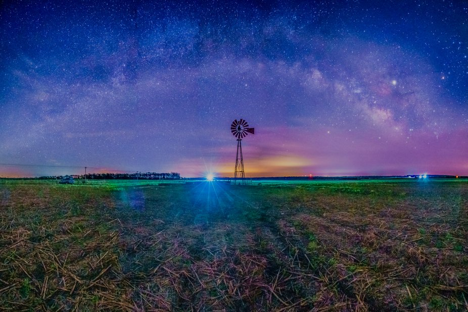 The Milky Way as a Rainbow over a soybean field and farm windmill near Waverly Mississippi. The w...