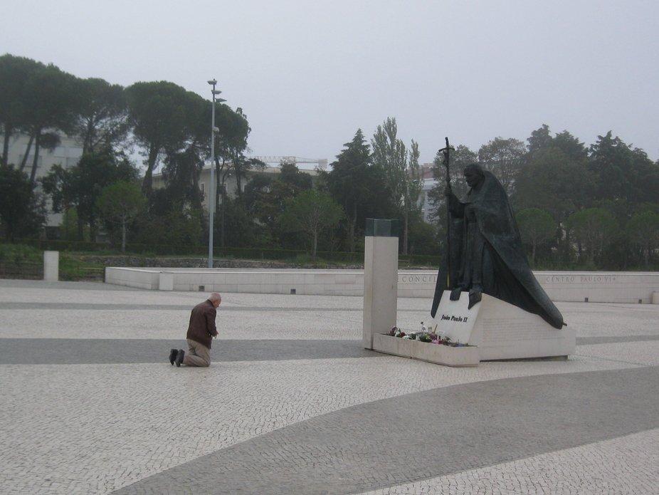 Hombre postrado frente al monumento a Juan Pablo II en Fátima.Portugal.