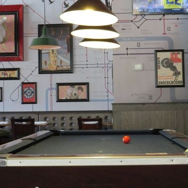 The pool table, illuminated by three, bright lights, beckons patrons to play pool. Let's go!