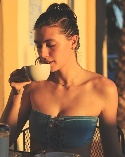 Meemie Gosselin drinking her espresso coffee in miami beach, florida with her dammya swimwear. Golden hour time