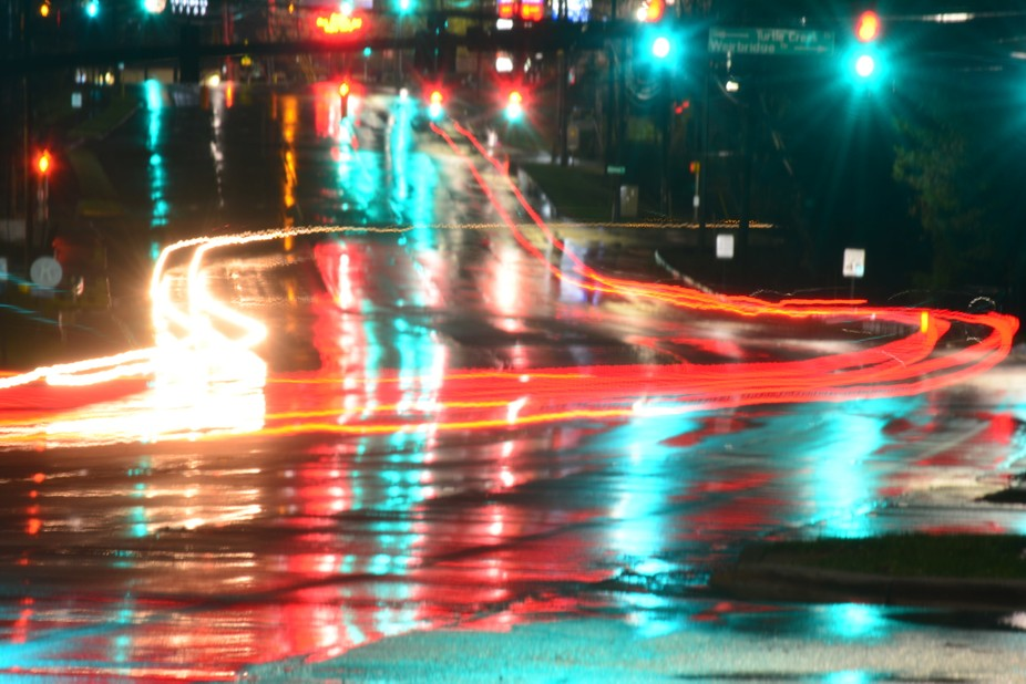 Rain reflects the colors of the road, and the lights all around