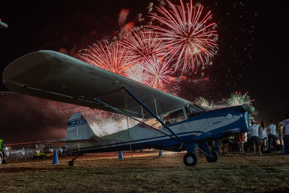 An historic Auster JB1 shot against the final fireworks display at the Australian international airshow.
