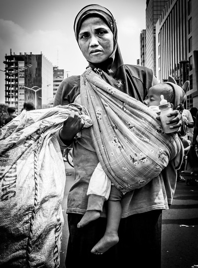 Woman, daughter and bag of plastic bottles