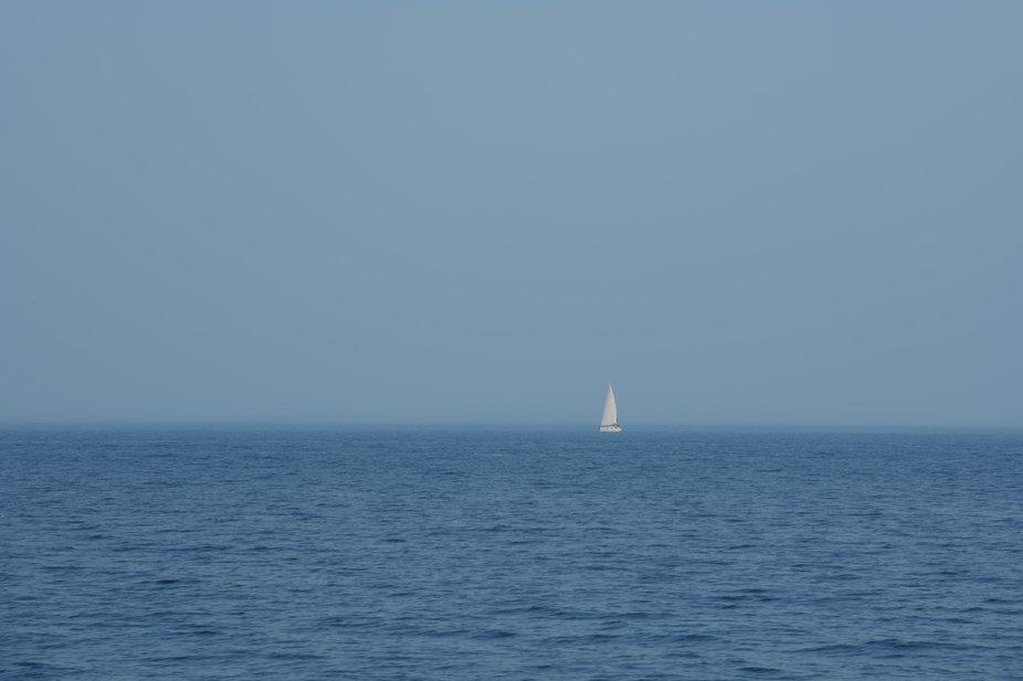 Single white sailboat in blue sea, minimalism