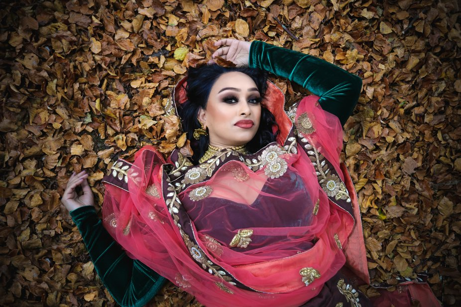 Amazing beautiful indian model laying on a floor of leaves in the forest.