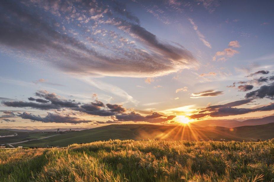 Golden sunset behinf the hills and fields of grass