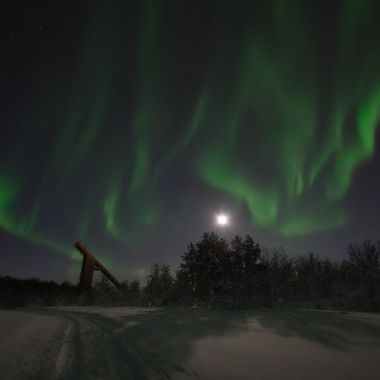 A nice winter evening in the city forest with the full moon and aurora borealis. Also with a ski jump hill in the background.