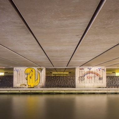 Underneath a viaduct with graffiti painted pillars. Shot with long exposure to smoothen the water of the canal. Purmerend, Holland.