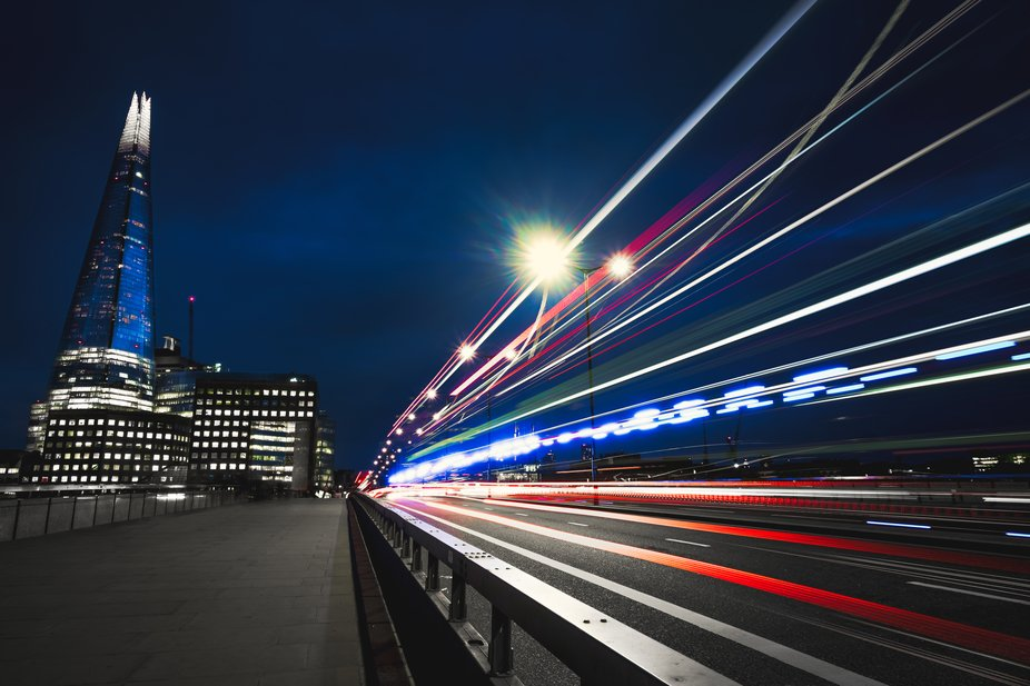 Long exposure shot of cars, busses and even and ambulance making their way across London Bridge