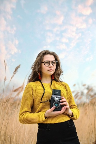 Girl in yellow with a film camera