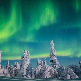 Auroras light up the sky over Riisitunturi National park in Lapland, Finland. Winter 2019.