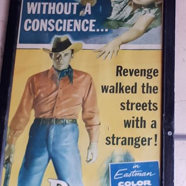 This poster is located at Gabby's Bar & Grill in Toronto. Joe Dakota is the handsome stranger who apparently comes to a town 'without a conscience' with the aim of seeking revenge. The picture of the woman leads us to speculate as to his motive.