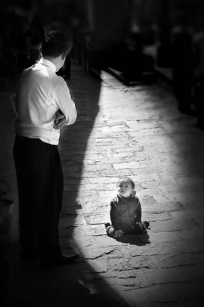 This kid was left alone for a few minutes and the waiter from nearby restaurant approached to talk with him,till his brother came back. Liked how the light eliminated everyone else. Used dodging and burning to emphasize the contrast