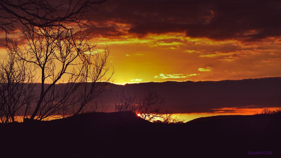 February sky with clouds, and the silhouettes of trees and hills made the sunset a spectacular si...
