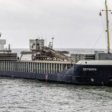 A stone carrying Vessel, the MV Ostborg loading stone at a quarry jetty.