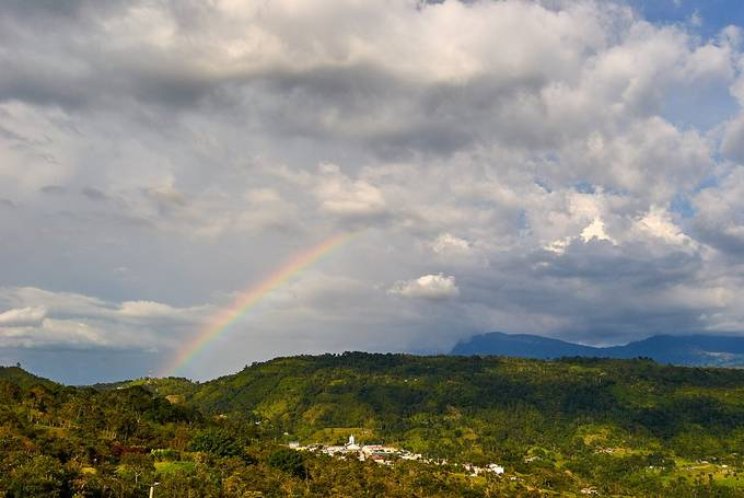 It's so amazing how beautiful rainbows are, but, looking closely, they seem to reflect light over things, like in this small town, it looks so bright with the rainbow... It was taken in San Juan de Rio Seco, about 3 hours from Bogota, Colombia. It's located on the Los Andes Mountains.