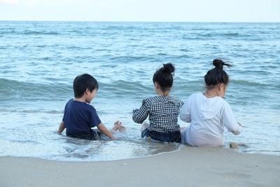 Three children chilled at the beach.