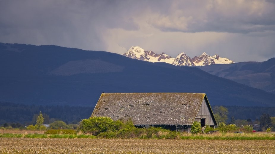 Storm clouds are gathering and coming toward this old barn. There is a small opening in the clouds providing a small peek at the mountains in the distance...