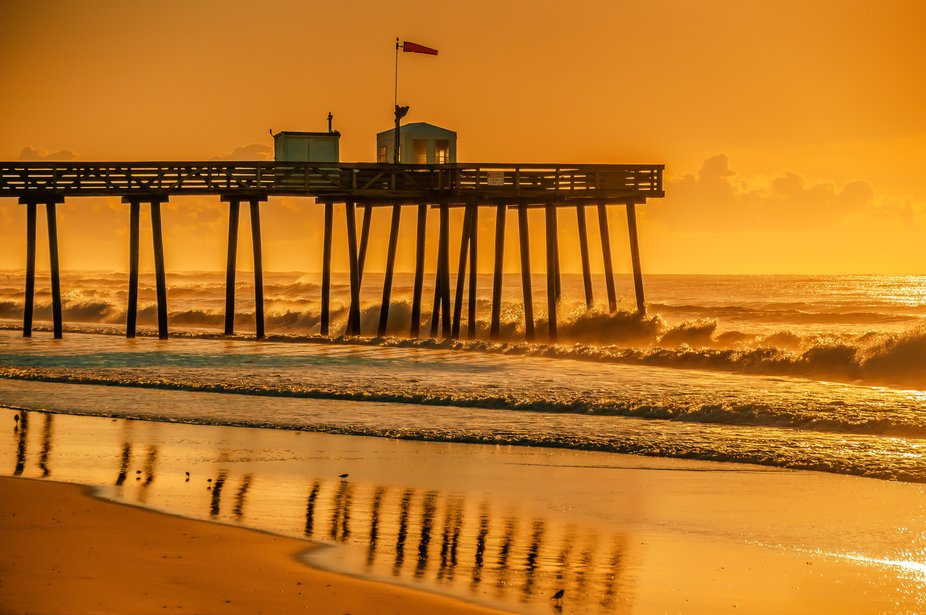 Sunrise on a August morning. Part of the pier reflecting on the wet sand.