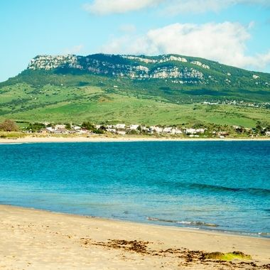 a tranquil beach scene looking at one of the hills surrounding bolonia in Andalucía, Spain
