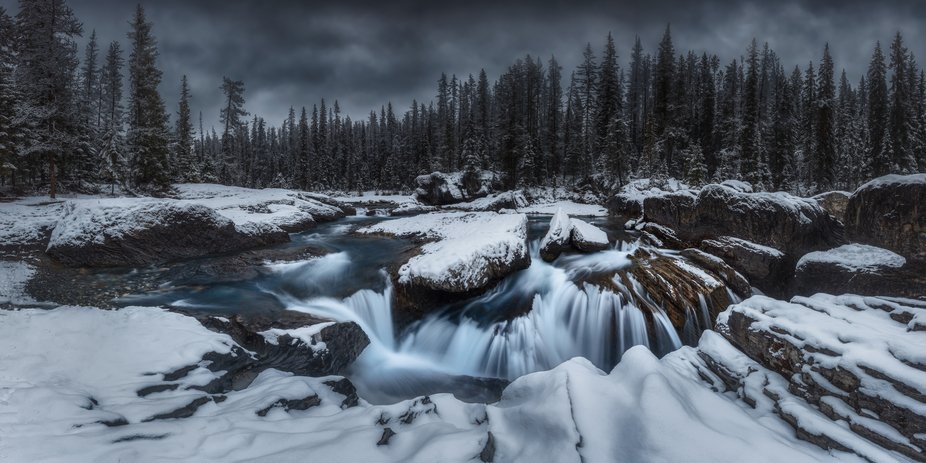 A dark afternoon in the Yoho National Park, deep blue water running through the Natural Bridge. I...