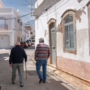 Two men walking the street in Fuseta, Portugal