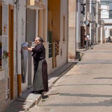 Old woman drying her laundry in front of her house in one of the many lovely streets in Fuseta, Portugal
