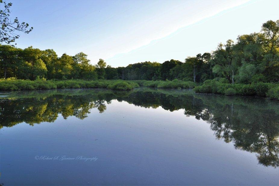 Glass-like surface of a small lake near Shaupeneak Ridge at sunrise