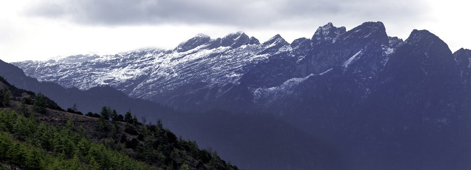 This image is 3 images stitched together of a mountain range in Bhutan