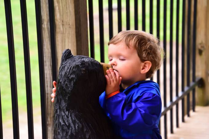 Little guy stealing a kiss  from a bear carving at Bear Sanctuary