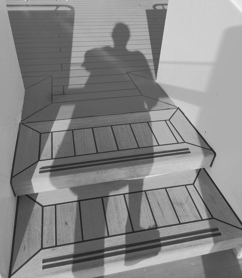 Ich habe meinen Schatten fotografiert da am Polarkreis die Sonne direkt von oben scheint. Die zeigt zwei Figuren die mit sich unzufrieden sind. Die linke versucht den Schatten zu sich zu ziehen um ihre Figur zu verbergen, die rechte hat hohe Schuhe an um als Modell zu wirken weil sie ja meistens schlank sein sollen. Unterschiedlicher kann die Gesellschaft nicht sein.