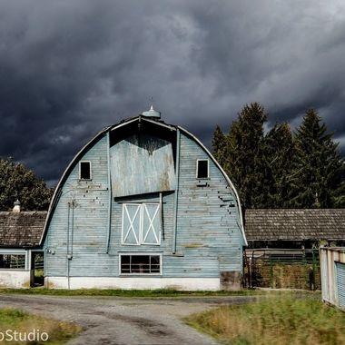 Blue barn against stormy skies
