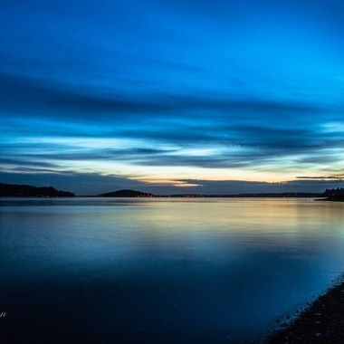 Stunning blues swept the sky during the blue hour this morning on Hood Canal. Hoods Head and the Hood Canal bridge is in the distance.