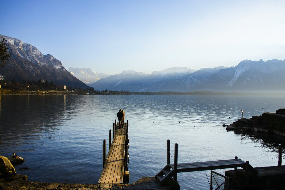 This is a view from one of the lakes in Switzerland, closest to Château de Chillon. The couple w...