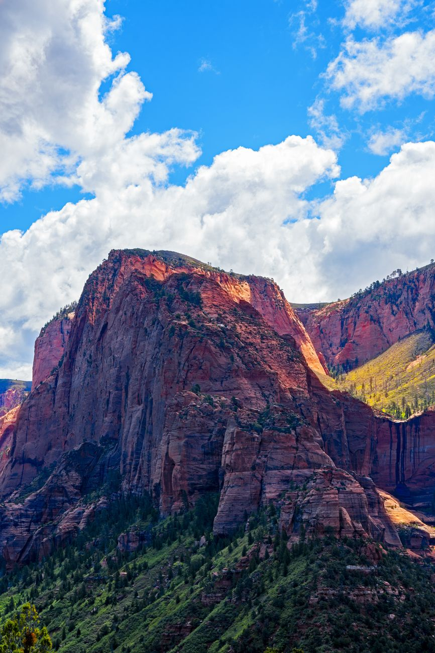 Kolob Canyon, Zion National Park. Tall red Rocky Mountain peak under a blue sky with white fluffy clouds. Sunlight on backside of mountain.