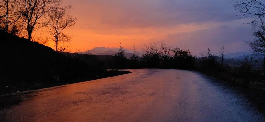 the sun is setting in rain