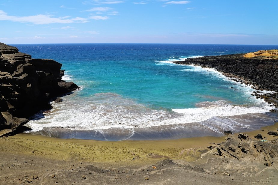Papakolea (green sand) Beach of the island of Hawaii surrounded by rocks with beautiful turquoise...