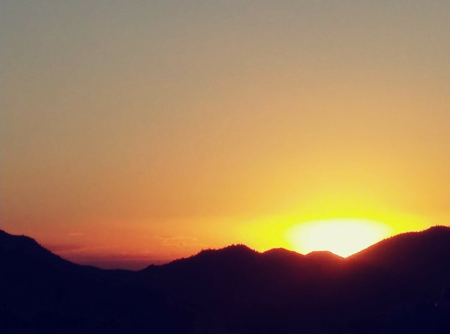 Captured this beautiful photo of the sun going down behind the desert mountains while hiking.