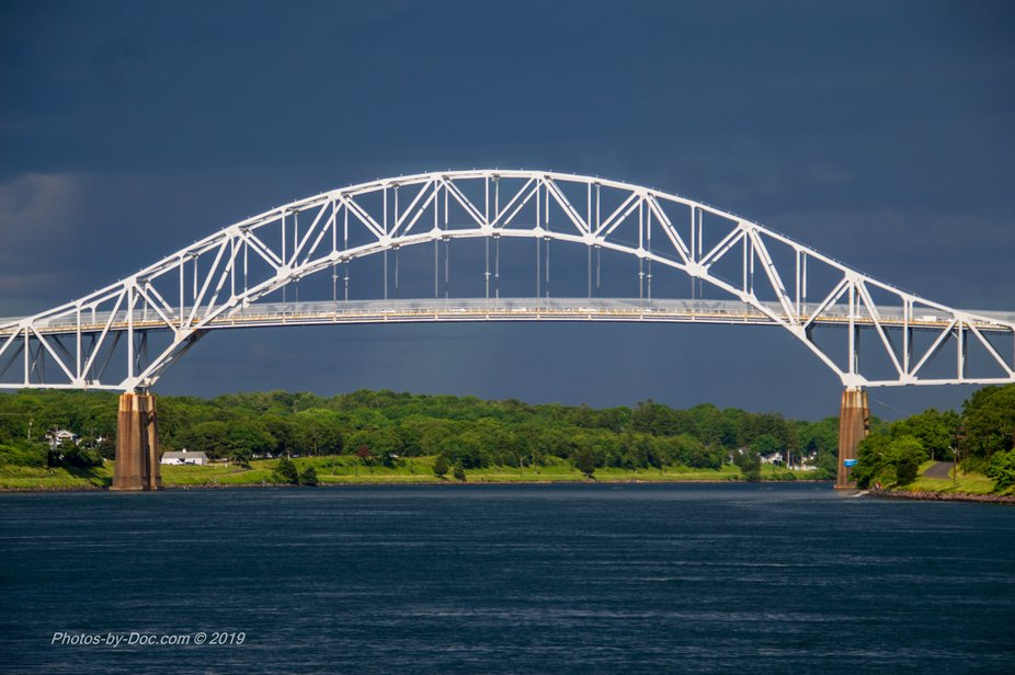 As a Thunderstorm rolls in The Sun shines it's light upon the west side of the bridge.