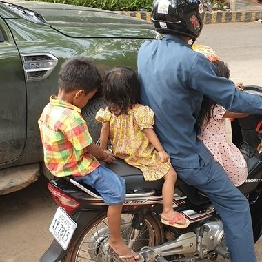 Captured this image in Siem Reap, Cambodia. It is amazing how many people can be fitted onto a scooter and other big items too! Child safety came to mind when I saw this! :-(