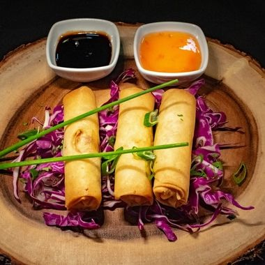 a trio of prawn spring rolls on a bed of red cabbage accompanied by a selection of sauces for dipping