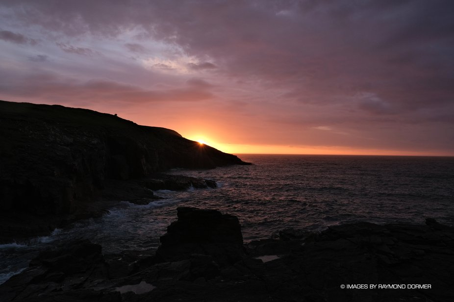 A beautiful sunrise at the Port of Ness, Isle of Lewis as the sun appears over the horizon it glo...