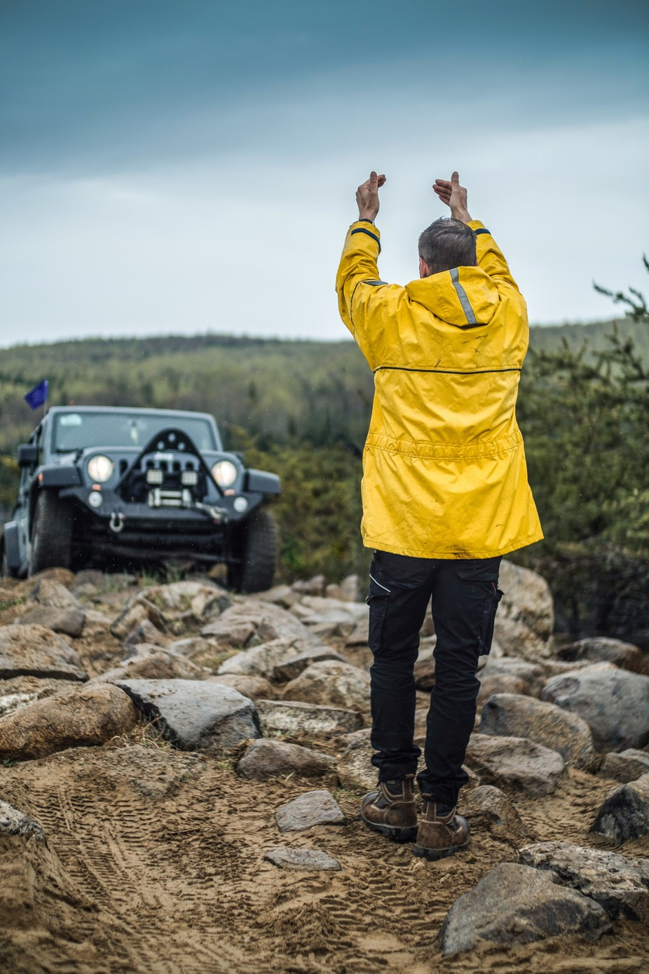 A guide ensures safe passage for a Jeeper on a rocky trail.
