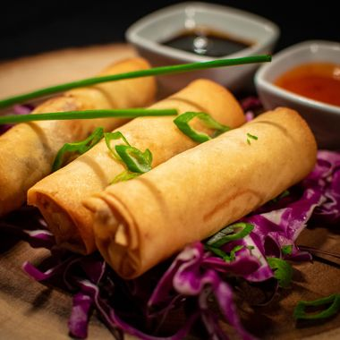 a selection of Chinese style spring rolls accompanied by a selection of sauces