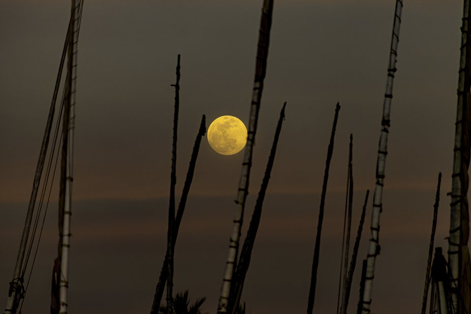 Rising diagonally upwards the moon was caught between two poles of a sail boat on a sunset river ...